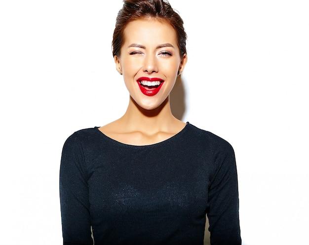 Donna di moda ammiccante sorridente allegra impazzendo in abiti neri casual con labbra rosse sul muro bianco