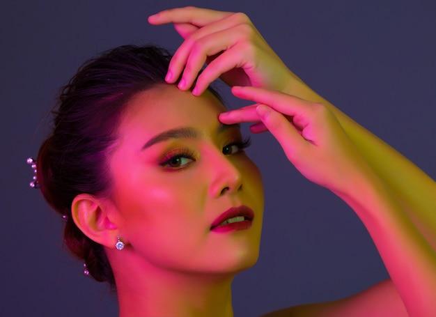 Donna di modello di alta moda nella posa variopinta delle luci intense