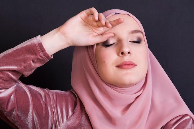 Donna di modello musulmana di eleganza che posa contro il contesto nero