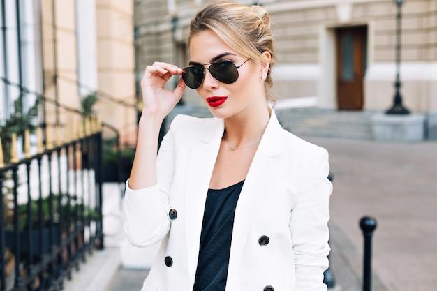 Donna di modo del ritratto in occhiali da sole con le labbra rosse sulla strada. sta cercando di fotocamera.