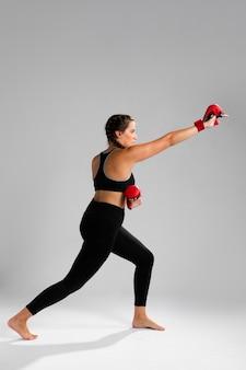 Donna di movimento di karatè che perfora con i guanti della scatola