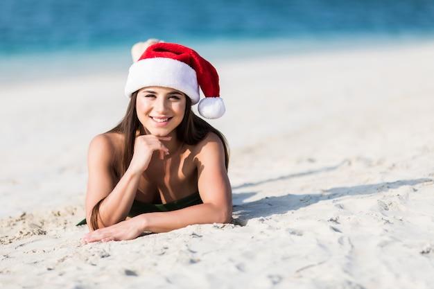 Donna di natale che si distende durante le feste della spiaggia di inverno. ragazza che sorride alla macchina fotografica durante la vacanza di viaggio che porta un cappello di santa.