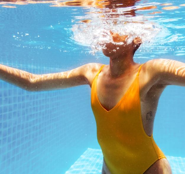 Donna di origine africana sott'acqua in piscina