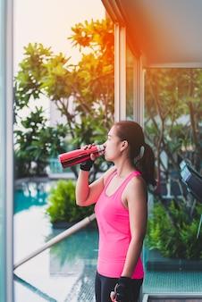 Donna di palestra che risolve l'acqua potabile al centro fitness. modello asiatico di forma fisica femminile dentro nella forma fisica