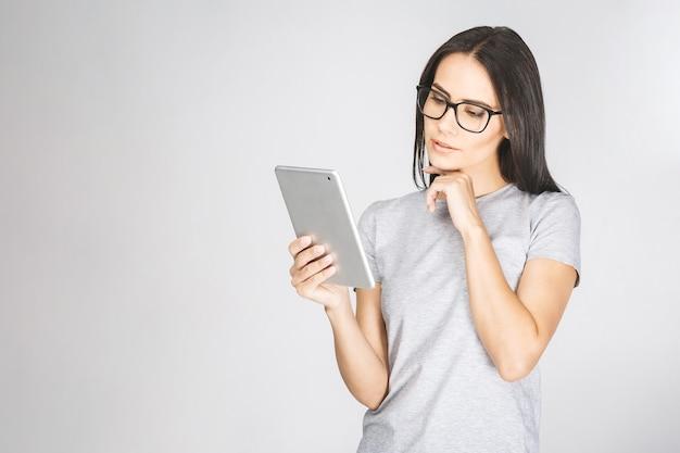 Donna di pensiero fiduciosa abbastanza affascinante in casual avendo tablet nelle mani