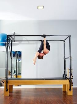 Donna di pilates in cadillac acrobatico sottosopra