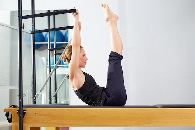 Donna di pilates in esercizio di reformer in palestra