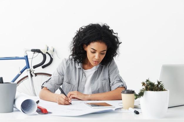Donna di razza mista concentrata con capelli ricci neri sul posto di lavoro