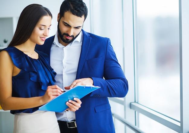 Donna di razza mista e il suo collega barbuto che utilizza il telefono per discutere di un progetto congiunto nella società di ufficio