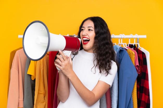 Donna di razza mista in un negozio di abbigliamento e in possesso di un megafono