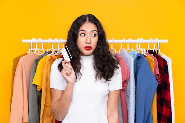 Donna di razza mista in un negozio di abbigliamento e in possesso di una carta di credito