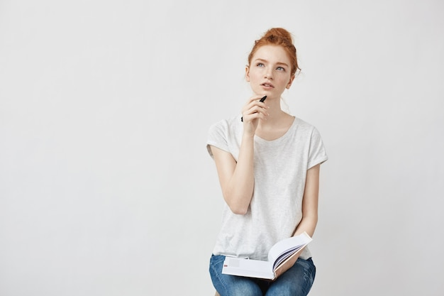 Donna di redhead che fa le note che pensano seduta