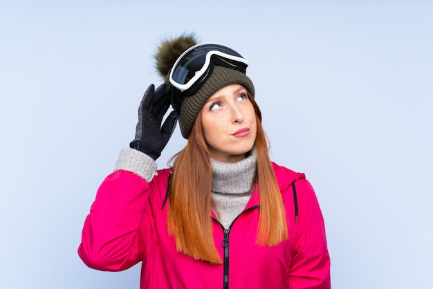 Donna di redhead dello sciatore con i vetri di snowboard sopra la parete blu isolata che ha dubbi e con l'espressione confusa del fronte
