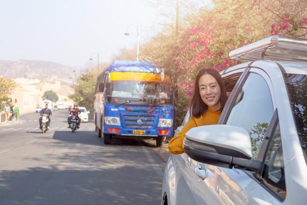 Donna di rilassamento sul roadtrip di estate che si appoggia fuori concetto di vacanza di viaggio della finestra di automobile.