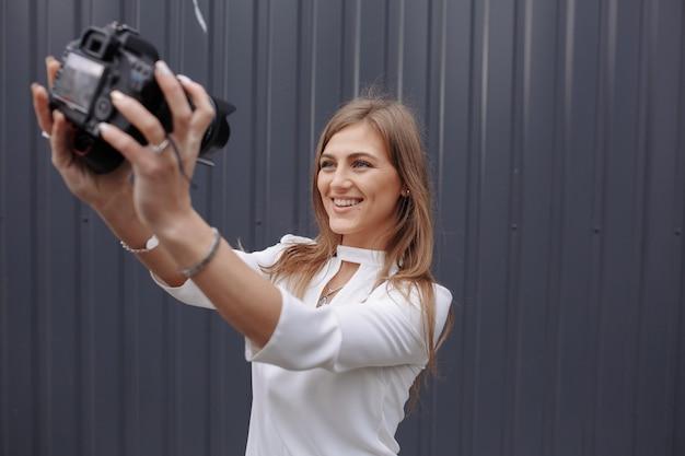 Donna di scattare una foto di se stessa con una macchina fotografica reflex