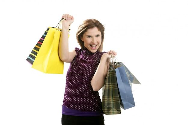 Donna di shopaholic con i sacchetti variopinti sopra bianco