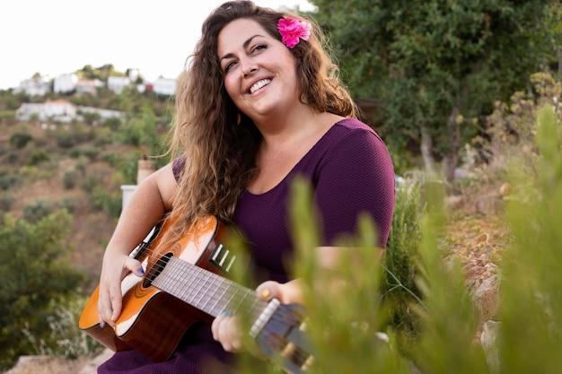 Donna di smiley all'aperto con la chitarra
