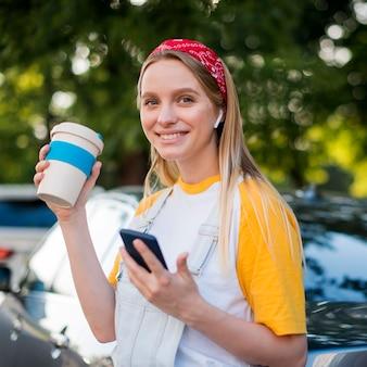 Donna di smiley all'aperto con la tazza e lo smartphone