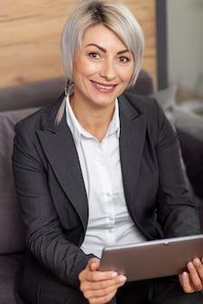 Donna di smiley alla compressa della tenuta dell'ufficio