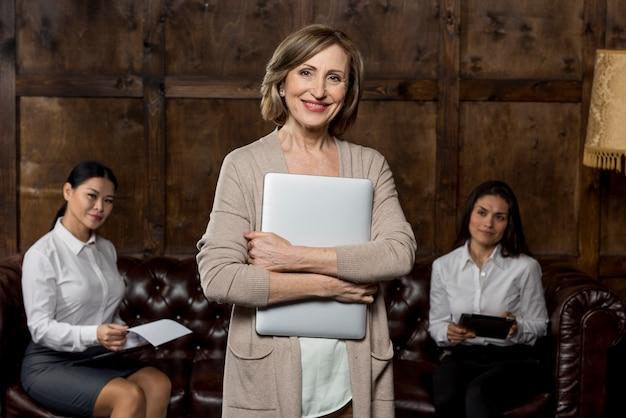 Donna di smiley alla riunione con il computer portatile