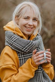 Donna di smiley che beve tè per riscaldarsi