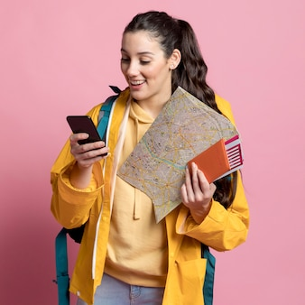 Donna di smiley che controlla il suo telefono mentre tiene una mappa e il suo passaporto