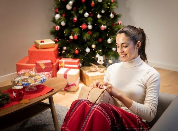 Donna di smiley che disimballa un regalo