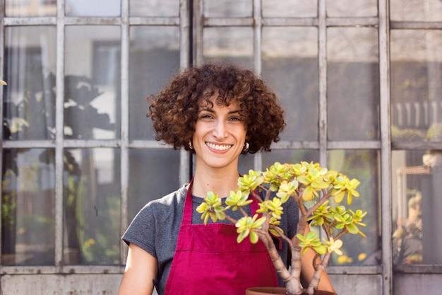 Donna di smiley che fa il giardinaggio all'interno