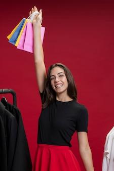 Donna di smiley che ostacola i suoi sacchetti della spesa