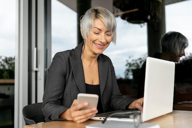 Donna di smiley che per mezzo di dispositivi elettronici