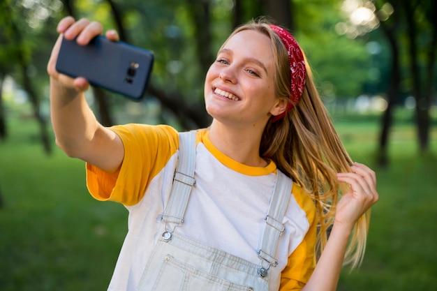 Donna di smiley che prende selfie all'aperto