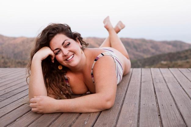 Donna di smiley che propone all'aperto in natura