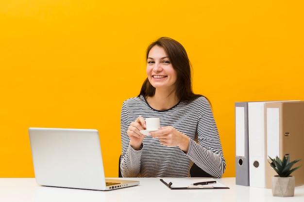Donna di smiley che propone alla sua scrivania mentre si tiene la tazza di caffè