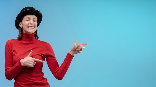 Donna di smiley che propone con il cappello mentre indica