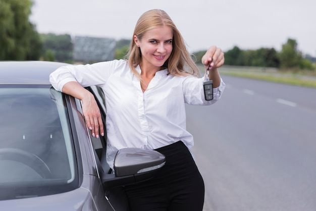 Donna di smiley che propone con le chiavi dell'automobile