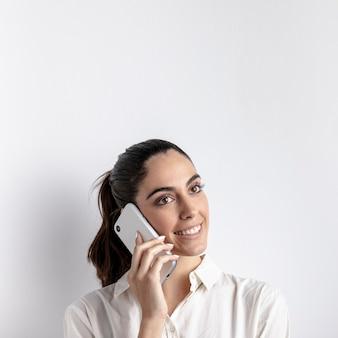 Donna di smiley che propone con lo smartphone