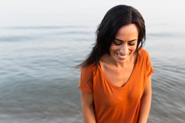 Donna di smiley che propone meravigliosamente alla spiaggia