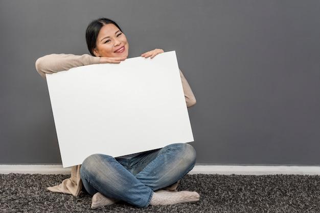 Donna di smiley che tiene foglio di carta bianco