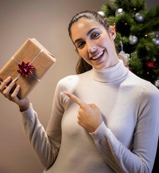 Donna di smiley che tiene un regalo