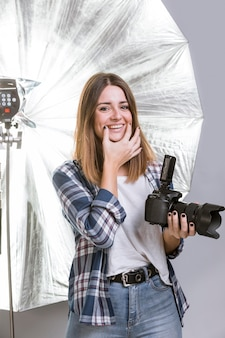 Donna di smiley che tiene una macchina fotografica professionale