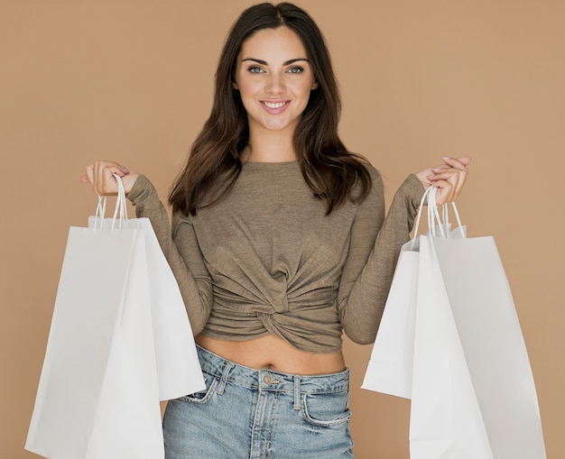 Donna di smiley con i sacchetti di shopping in entrambe le mani