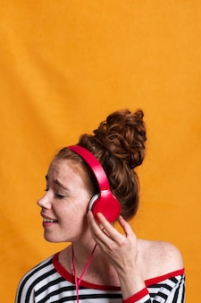 Donna di smiley del primo piano che ascolta la musica con le cuffie