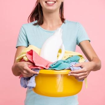 Donna di smiley del primo piano che tiene un cestino di lavanderia