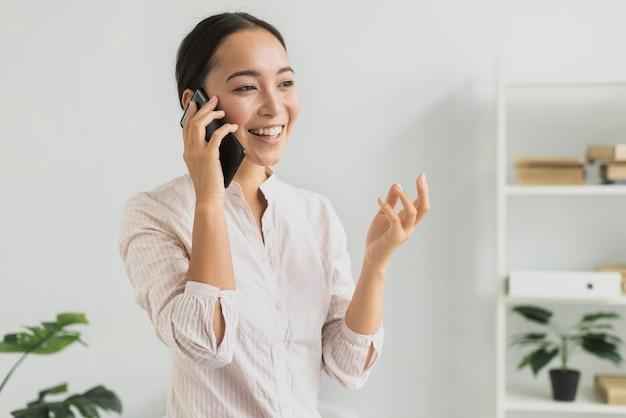 Donna di smiley del ritratto che parla sopra il telefono