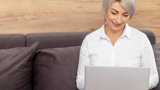 Donna di smiley dell'angolo alto che lavora al computer portatile
