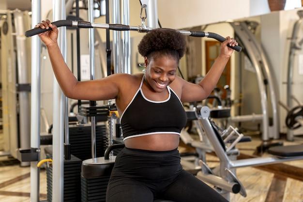 Donna di smiley dell'angolo alto che risolve alla ginnastica