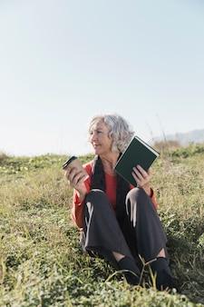 Donna di smiley della foto a figura intera con il libro all'aperto