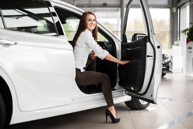 Donna di smiley di angolo basso che fa un passo fuori dall'automobile