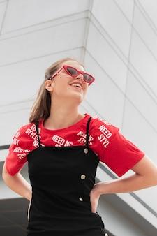 Donna di smiley di angolo basso con gli occhiali da sole