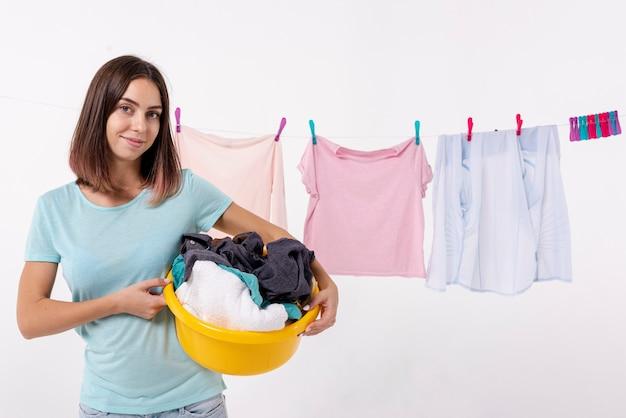 Donna di smiley di vista frontale che tiene un cestino di lavanderia